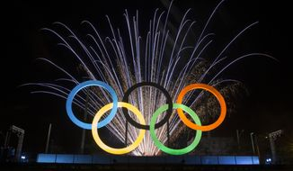 Fireworks explode behind the Olympic rings during their inauguration ceremony on May 20, 2015, at Madureira Park in Rio de Janeiro, Brazil. (Associated Press)