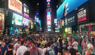 Crowds of visitors linger in New York's Times Square on July 16, 2016. (Associated Press) **FILE**