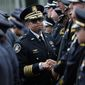 Detroit Police Chief James Craig (center) greets Dallas police officers after the funeral for one of the city's five officers slain this month by a gunman. Police officers across the country are facing even more threats. (Associated Press)