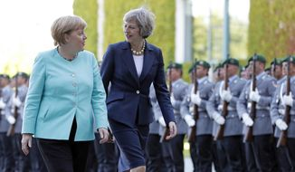 German Chancellor Angela Merkel, left, and British Prime Minister Theresa May walk on the red carpet during a military welcoming ceremony at the chancellery in Berlin Wednesday, July 20, 2016, on May's first foreign trip after being named British Prime Minister. (AP Photo/Michael Sohn)