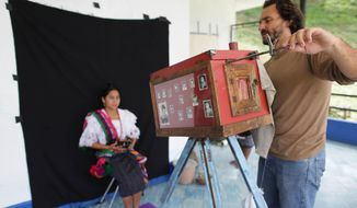 FILE - In this Aug. 8, 2011 file photo, Associated Press photographer Rodrigo Abd uses a 19th-century style wooden box camera as he photographs a participant of the Rabin Ajau National Folkloric Festival in Guatemala City. Participants had to hold still for up to two minutes as Abd made exposures with light shining directly from the lens onto photo paper inside the box camera. Abd and three other journalists in Brazil, Colombia and El Salvador won the 2016 Maria Moors Cabot Prize, which recognizes excellence in coverage of Latin America and the Caribbean. (AP Photo/Jesus Cuque Lopez, File)