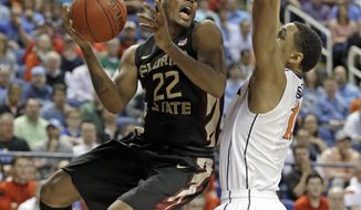 FILE - In this March 12, 2015, file photo, Florida State's Xavier Rathan-Mayes (22) drives against Virginia's Evan Nolte (11) during the second half of an NCAA college basketball game in the quarterfinals of the Atlantic Coast Conference tournament in Greensboro, N.C. Rathan-Mayes is putting more of a focus on defense during the offseason as he tries to get Florida State back to the NCAA tournament for the first time since 2012.  (AP Photo/Bob Leverone, File)