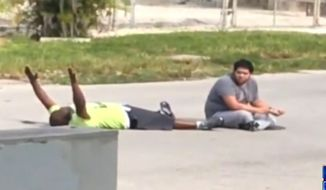 Video shows Charles Kinsey, 47, telling police with his hands in the air that he does not have a weapon and that he is a caretaker for an autistic man. Mr. Kinsey was shot in the leg moments later. (WSVN-7 Miami screenshot)