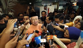 Malaysian Prime Minister Najib Razak is surrounded by journalists after attending an Eid Al-Fitr open house event in Kuala Lumpur, Malaysia, Thursday, July 21, 2016. Pressure mounted Thursday on Najib, with lawmakers demanding he go on leave and be held accountable after U.S. officials initiated action to seize more than $1 billion they say was stolen from a state investment fund by people close to the premier. (AP Photo/Vincent Thian)
