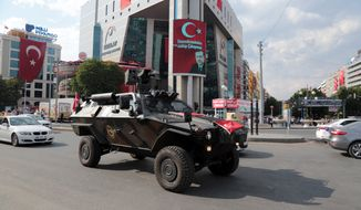 A police APC drives in Kizilay Square with a poster of Turkey's President Recep Tayyip Erdogan in the background in Ankara, Turkey, Thursday, July 21, 2016. The stunning sweep of Turkeys crackdown following an attempted coup last week forces questions about how far President Recep Tayyip Erdogan will go to cement his personal power at the expense of accepted democratic ideals. (AP Photo/Burhan Ozbilici)