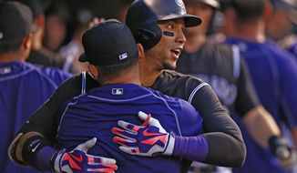 Colorado Rockies' Carlos Gonzalez celebrates a three run home run hit off Atlanta Braves starting pitcher Mike Foltynewicz with teammates in the dugout during the sixth inning of a baseball game, Thursday, July 21, 2016, in Denver. (AP Photo/Jack Dempsey)