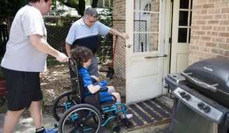 ADVANCE FOR USE SATURDAY, JULY 23 - In this Friday, July 1, 2016 photo, Grant McNall, left, helps August McNall up a ramp and into their house as he arrives at his home in Janesville, Wis., from an almost two month stay in the hospital following a diagnosis of pediatric onset multiple sclerosis. (Angela Major/The Janesville Gazette via AP)