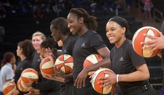 FILE - In this Wednesday, July 13, 2016 file photo, members of the New York Liberty basketball team await the start of a game against the Atlanta Dream, in New York. The WNBA has fined the New York Liberty, Phoenix Mercury and Indiana Fever and their players for wearing plain black warm-up shirts in the wake of recent shootings by and against police officers. All three teams were fined $5,000 and each player was fined $500. While the shirts were the Adidas brand - the official outfitter of the league - WNBA rules state that uniforms may not be altered in any way. (AP Photo/Mark Lennihan, File)