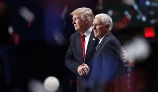 Republican presidential Donald Trump and Republican vice presidential nominee Mike Pence celebrate after Mr. Trump's acceptance speech Thursday, the final day of the Republican National Convention in Cleveland. (Associated Press)