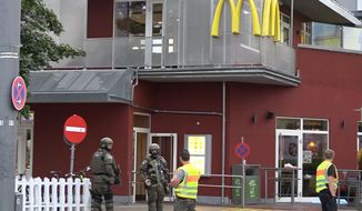 In this grab taken from video, police officers stand outside a McDonald's restaurant, near the mall, in Munich, Germany, Friday, July 22, 2016. A manhunt was underway Friday for a shooter or shooters who opened fire at a shopping mall in Munich, killing and wounding several people, a Munich police spokeswoman said. The city transit system shut down and police asked people to avoid public places. (NONSTOP NEWS via AP)
