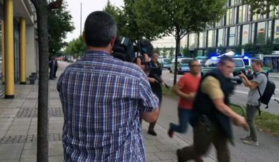 Armed police move past onlooking media responding to a shooting at a shopping center in Munich, Germany, Friday, July 22, 2016. Munich police confirm shots have been fired at Olympia Einkaufszentrum shopping center but say they don't have any details about casualties. Police are responding in large numbers. (AP Photo/APTV)