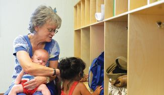 In this June 28, 2016 photo, the Sheridan Press Child care provider Nancy Weaver holds Klayton Pearce as she keeps a toddler from pulling an object from a cubby hole at the Tongue River Child's Place in Ranchester, Wyo. Staff at the facility have been working with 4Kids on training as part of a pilot program. (Justin Sheely/Sheridan Press via AP)