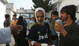Afghans help a man who was injured in a deadly explosion that struck a protest march by ethnic Hazaras, in Kabul, Afghanistan, Saturday, July 23, 2016. Afghan Health Ministry officials say tens of people have been killed and over 200 wounded in the bombing Saturday, that was claimed by the Islamic State group according to a statement posted on the IS-linked Aamaq online news agency. The protesters Saturday were demanding that a major regional electric power line be routed through their impoverished home province. (AP Photo/Rahmat Gul)