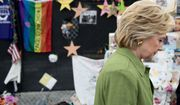 Democratic presidential candidate Hillary Clinton walks past photographs of victims of the Pulse nightclub shooting after visiting a memorial outside of the Pulse nightclub in Orlando, Friday, July 22, 2016, which was the site of a June 12th shooting that kill 49 people. (AP Photo/Andrew Harnik)
