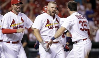 'St. Louis Cardinals' Matt Adams, center, is congratulated by teammates Adam Wainwright, left, and Greg Garcia, right, after hitting a walk-off home run to defeat the Los Angeles Dodgers 4-3 in the 16th inning of a baseball game early Saturday, July 23, 2016, in St. Louis. (AP Photo/Jeff Roberson)