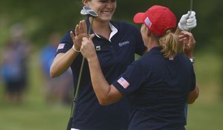 Lexi Thompson, left, and Cristie Kerr congratulate each other after finishing second in their pool Saturday, July 23, 2016, during the third round of the LPGA's UL International Crown golf tournament in Gurnee, Ill. The United States advanced to Sunday's singles round. (Morgan Timss/Daily Herald via AP)