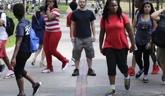 In this Friday, July 22, 2016 photo, Collin Allen, the creator of 'White Men for Black Lives', poses on the Freedom Trail in Boston Common, as a group of summer camp children walk past, in Boston, Mass. Some white Americans say they're being spurred to action by the shootings of black men by officers in Minnesota and Louisiana after long sitting in silence. (AP Photo/Charles Krupa)