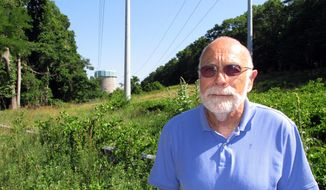 In this July 12, 2016 photo, Sid Bail, president of the Wading River Civic Association, poses outside the defunct Shoreham Nuclear Power Plant in Wading River, N.Y. Bail is among those who are opposing a proposal to build a solar energy project on the Shoreham property. The plan, which still needs regulatory approvals, would require cutting down 350 acres of trees. (AP Photo/Frank Eltman)