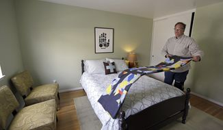FILE - In this Oct. 16, 2015 file photo, Bruce Bennett folds a blanket in a room that he makes available to rent in he and his husband's home in San Francisco. Supervisors in a city nearly synonymous with the internet say an ordinance requiring Airbnb and other short-term rental platforms to list only legal units or face steep fines is a simple change to existing law. Airbnb, however, says the new regulation challenges the heart of what makes the internet the flourishing, free-wheeling frontier it is: that internet platforms, such as Facebook and Twitter, cannot be sued or punished for the content posted by third-party hosts. (AP Photo/Ben Margot, File)