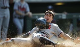 Atlanta Braves' Chase d'Arnaud slides safely across home plate as he scores on a double hit by Freddie Freeman off Colorado Rockies relief pitcher Gonzalez Germen in the seventh inning of a baseball game Sunday, July 24, 2016, in Denver. Colorado won 7-2. (AP Photo/David Zalubowski)
