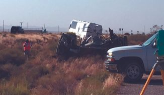 The scene of a bus crash is surveyed Sunday, July 24, 2016, on a highway in northwestern Arizona. A Dallas Cowboys bus collided with another vehicle and authorities say at least one person was killed. Team spokesman Rich Dalrymple confirmed a Cowboys bus was one of two vehicles involved in the crash Sunday on U.S. 93. (Cody Davis/Kingman Daily Miner via AP)