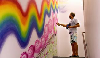 In this 2013 photo provided by RxArt, Kenny Scharf paints a hallway with his art at Kings County Hospital Center in the Brooklyn borough of New York. RxArt commissions leading contemporary artists to create original artworks on walls, ceilings, floors - even medical equipment - of pediatrics wards across the country, with the mission of making pediatrics facilities less intimidating and help young patients heal through the power of visual art. (RxArt via AP)