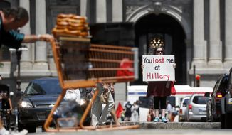 An anti-Hillary Clinton demonstrator stands with a sign in downtown Philadelphia, Monday, July 25, 2016, on the first day of the Democratic National Convention. (AP Photo/John Minchillo)