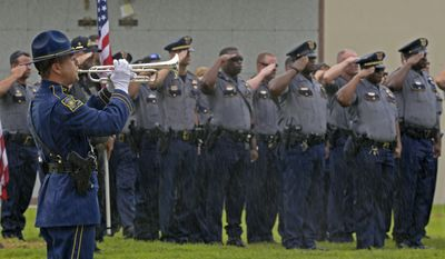 """Members of the Baton Rouge Police Department salute as a member of the Louisiana State Police Honor Guard, left, plays """"Taps"""" through driving rain during funeral services for Baton Rouge police Cpl. Montrell Jackson in Baton Rouge, La., Monday, July 25, 2016. Jackson, slain by a gunman who authorities said targeted law enforcement, is the last of the three Louisiana law enforcement officers killed in last week's ambush to be buried. (Hilary Scheinuk/Baton Rouge Advocate via AP) ** FILE **"""