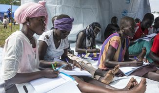 In this photo released by United Nations Mission in South Sudan (UNMISS) on Monday, July 25, 2016, women participate at Friendship Primary and Nursery School, a makeshift school comprising of several classrooms that has been opened for internally displaced people in a transit area, at the United Nations Mission compound in Tomping, Juba, South Sudan. The initiative is providing basic education to about 900 displaced children and adolescents. (Isaac Billy/UNMISS via AP)