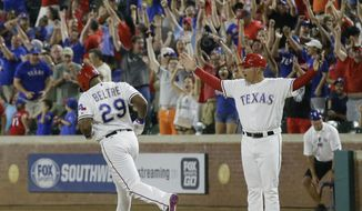 Texas Rangers first base coach Hector Ortiz, right, and fans cheer as Adrian Beltre (29) runs the bases after hitting a game winning two-run homer during the ninth inning of a baseball game against the Oakland Athletics in Arlington, Texas, Monday, July 25, 2016. The Rangers won 7-6. (AP Photo/LM Otero)
