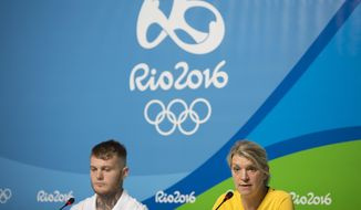 Australia's delegation head Kitty Chiller, right, and boxer Daniel Lewis listen to questions during a press conference in the Olympic Park in Rio de Janeiro, Brazil, Monday, July 25, 2016. The head of the Australian delegation says that despite a delay of several days she expects her delegation to move into the athletes village on Wednesday. (AP Photo/Felipe Dana)