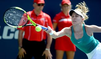 CORRECTS TO FIRST ROUND- Eugenie Bouchard of Canada returns the ball against Lucie Safarova of the Czech Republic during women's first round Rogers Cup tennis action in Montreal on Tuesday, July 26, 2016. (Paul Chiasson/The Canadian Press via AP)