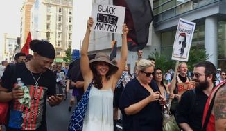 Actress Ashley Judd holds up a sign of Black Lives Matter as she joined the Philly REAL Justice group marching in Philadelphia on Tuesday, July 26, 2016. Judd stopped on Broad Street in Philadelphia with tears in her eyes while watching a protest against police brutality. (AP Photo/AP Video)
