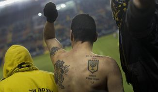 "In this Tuesday, Jan. 29, 2013 file photo, Beitar Jerusalem F.C. soccer supporters watch a State Cup soccer match against Maccabi Umm al-Fahm F.C. at the Teddy Stadium in Jerusalem. Israeli police say they have arrested dozens of members of an extremist soccer fans' group. Police spokeswoman Luba Samri said on Tuesday, July 26, 2016 that 56 suspected members of the ""La Familia"" group of Beitar Jerusalem fans were arrested in an overnight raid. (AP Photo/Bernat Armangue, File)"