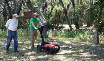 In this undated image provided by Amanda Thompson with the University of Georgia shows archeologists Chester DePratter, left, with the University of South Carolina and Victor Thompson, right, of the University of Georgia, running ground penetrating radar across a land grid. Archaeologists have found the location of a long-sought Spanish fort on the South Carolina coast near Beaufort. The location of San Marcos, one of five forts that operated during the 21-year history of the early Spanish settlement of Santa Elena, has been found on Parris Island. (Amanda Thompson/University of Georgia via AP)