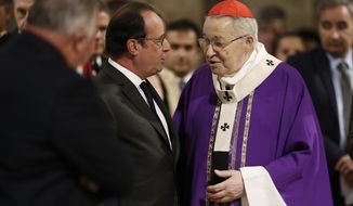 French President Francois Hollande speaks with French Archbishop of Paris Cardinal Andre Vingt-trois, right, before a mass to pay tribute to French priest Father Jacques Hamel at the Notre-Dame Cathedral in Paris, France, Wednesday, July 27, 2016. Father Jacques Hamel was killed on Tuesday in an attack on a church at Saint-Etienne-du-Rouvray near Rouen, Normandy, that was carried out by assailants linked to Islamic State. (Benoit Tessier/Pool Photo via AP)