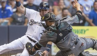 Milwaukee Brewers' Scooter Gennett is tagged out by Arizona Diamondbacks' Welington Castillo during the first inning of a baseball game Tuesday, July 26, 2016, in Milwaukee. (AP Photo/Tom Lynn)