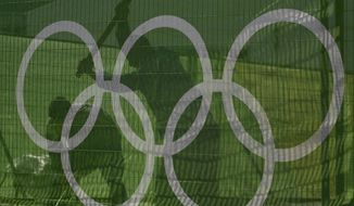 Workers secure a fence at Olympic Park as they make preparations for the upcoming Rio Olympics in Rio de Janeiro, Brazil, Wednesday, July 27, 2016. (AP Photo/Charlie Riedel)