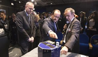 In this Wednesday, Nov. 12, 2014, file photo, French President Francois Hollande, center, with French astrophysicist Francis Rocard look at a model of Rosetta lander Philae, as they visit the Cite des Sciences at La Villette in Paris during a broadcast of the Rosetta mission as it orbits around comet 67/P Churyumov-Gersimenko. The European Space Agency says Wednesday July 27, 2016, it is switching off its radio link to the probe that landed on a comet, after receiving no signal from the lander for a year. (AP Photo/Jacques Brinon, Pool, file)