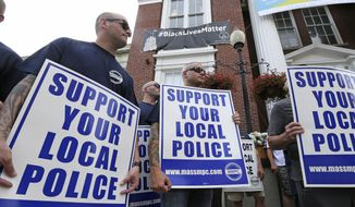 Police officers and their supporters picket outside Somerville City Hall, Thursday, July 28, 2016, in Somerville, Mass. Somerville Mayor Joe Curtatone is promising not to remove a Black Lives Matter banner from City Hall despite complaints from police officers in the state. (AP Photo/Charles Krupa)