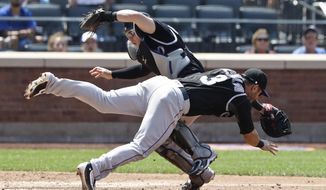 Colorado Rockies catcher Tony Wolters, left, and Daniel Descalso collide as Wolters catches a foul ball by New York Mets' Wilmer Flores during the fourth inning of a baseball game Thursday, July 28, 2016, in New York. (AP Photo/Frank Franklin II)