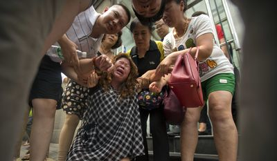 A woman cries while while demonstrating with relatives of passengers aboard Malaysia Airlines Flight 370 outside the Ministry of Foreign Affairs in Beijing, China, Friday, July 29, 2016. Several dozen relatives gathered at the ministry on Friday to hand over a letter of protest amid the recent announcement that the meticulous ocean search operations for the missing flight would soon be suspended. (AP Photo/Mark Schiefelbein)