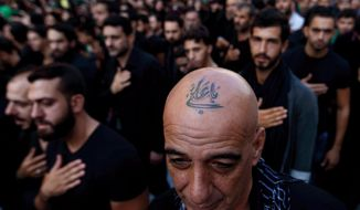 "In this Saturday, Oct. 24, 2015 photo, a Lebanese Shiite supporter of Hezbollah with a tattoo on his head that reads in Arabic, ""Oh Ali"", beats his chest during the holy day of Ashoura, in the southern suburb of Beirut, Lebanon. A growing number of Shiite Muslims in Lebanon are getting tattoos with religious and other Shiite symbols since the civil war in neighboring Syria broke out five years ago, fanning sectarian flames across the region. (AP Photo/Hassan Ammar)"