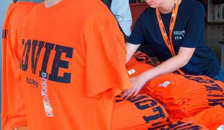 ADVANCE FOR USE SUNDAY, JULY 31, 2016 AND THEREAFTER - In this June 28, 2016 photo, Game Day Spirit cashier Heather Orland folds a display of Lovie t-shirts at the business in Champaign, Ill. Across the board,  all things Illini football, from tickets to T-shirts, are trending upward in Champaign. Call it the Lovie Smith Effect. Since the former Chicago Bears coach was announced as the new man in charge of Illinois football, the buzz surrounding the program has remained constant, and it will only continue to grow as Smith gets closer to coaching his first game,(Robin Scholz/The News-Gazette via AP )