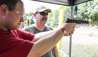 FOR RELEASE SATURDAY, JULY 30, 2016, AT 3:01 A.M. EDT. - Daniel Walmer, a reporter for the Lebanon Daily News, shoots a Smith & Wesson .22 compact pistol with a Silencerco Osprey Micro suppressor at Lanco Tactical's Suppressor Day at the Lebanon County Police Combat Pistol Club on Sunday, July 10, 2016.( Jeremy Long/Lebanon Daily News via AP)