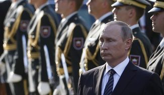 Russian President Vladimir Putin attends a ceremony at a Zale Cemetery in Ljubljana, Slovenia, Saturday, July 30, 2016. Slovenia, which has joined sanctions against Russia for its annexation of Crimea and meddling in Ukraine, has been very careful to portray Putin's visit on Saturday as strictly informal and not against the EU policies. (AP Photo/Darko Vojinovic)