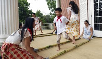 ADVANCE FOR WEEKEND EDITIONS JULY 30-31 - In this Monday, June 27, 2016 photo, Juliana Gonzalez, left, and Ally Pendon, right, tap the sticks as Brienn Daniel Ayerdi, second from left, and Lexi Gowan demonstrate Tinikling, the national dance of the Philippines at Heritage Park in Chattanooga, Tenn. The first wave of Chattanooga's Filipino immigrants were nursing students who came here back in the 1970s to attend school and fill America's urgent need for nurses at the time. Filipino nurses still come here to study but so do Filipino engineers, teachers and other professionals. (Angela Lewis Foster/Chattanooga Times Free Press via AP)
