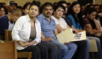 In this photo taken Wednesday, July 13, 2016 Esperanza Moreno, left, listens carefully during a Faith Action ID drive at Holy Family Catholic Church in Hillsborough, N.C. Moreno, of Durham, was one of more than 200 people with no legal U.S. identification learning how to use their new $10 ID cards to communicate with police. The FaithAction ID program has issued more than 7,000 ID cards, recognized by police and some local organizations in 16 cities and 9 counties. (AP Photo/Gerry Broome)