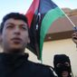 Libyan security forces stand in front of the security headquarters, one showing his weapon with a Libyan flag, in the western city of Sabratha, Libya, Saturday, Feb. 20, 2016. American fighter-bombers struck an Islamic State militant training camp in rural Libya near Sabratha Friday, killing dozens. Serbian officials say two Serbian embassy staffers who had been held hostage since November are believed to have been killed in the airstrikes. Washington and its European allies are seeking to end the interminable divisions among Libyan factions to form a unity government that the West can support in fighting the jihadis. (AP Photo/Mohamed Ben Khalifa)