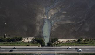In this July 5, 2016, file photo, cars drive above sewage flowing from the suburb of Sao Goncalo into Guanabara Bay, across the bay from Rio de Janeiro, Brazil. Throughout Brazil, sewage treatment has lagged dramatically, meaning that so-called 'black tongues' of fetid, sewage-filled water are common on beaches across the country. (AP Photo/Felipe Dana)